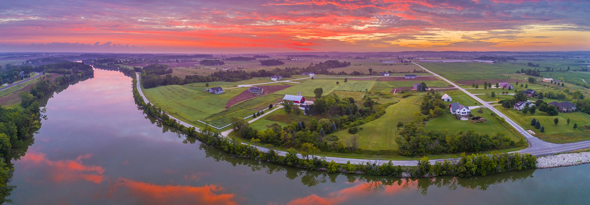 Red sky reflected in tranquil river at dawn, panoramic aerial view.